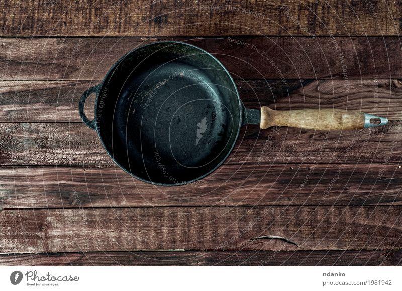 Schwarze Gusseisenbratpfanne auf einer braunen Holzoberfläche Geschirr Pfanne Design Tisch Küche Restaurant Werkzeug Metall oben Sauberkeit schwarz Kopie