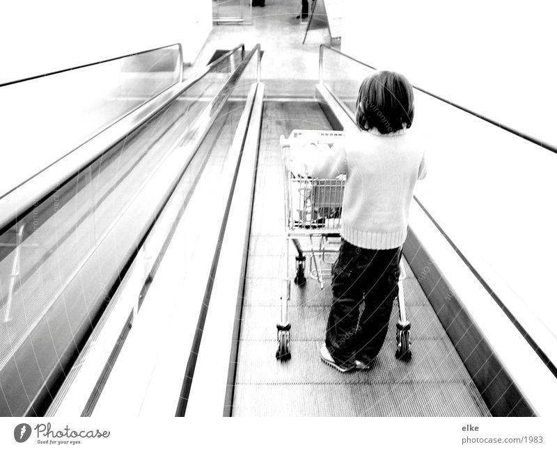 Einkaufsequenz 1 Rolltreppe Einkaufswagen Kind schieben Supermarkt Mensch Konsum Schwarzweißfoto