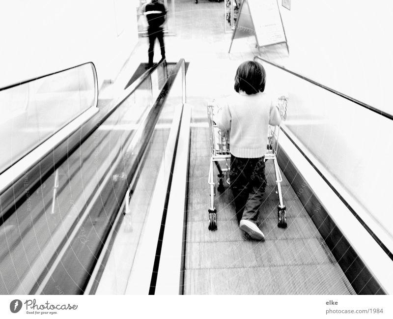 Einkaufsequenz Rolltreppe Einkaufswagen Kind kaufen schieben Supermarkt Mensch Schwarzweißfoto