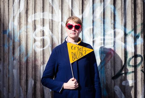 Stolz wie Bolle elegant Feste & Feiern Frau Erwachsene Mauer Wand Brückenpfeiler Betonwand Sonnenbrille Zeichen Fahne Schilder & Markierungen trotzig bizarr
