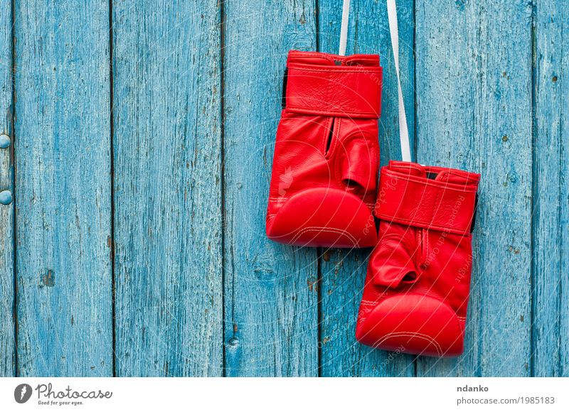 Paar rote Boxhandschuhe, die an einem Nagel hängen Sport Sportveranstaltung Erfolg Handschuhe Holz retro blau Konkurrenz Objektfotografie Kick Kopie Kraft