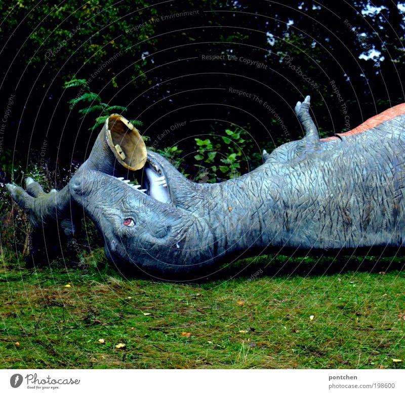Zerstörte Figur eines tyrannosaurus rex liegt  im Gras und hat eigenes Bein im Mund. Verlassener Freizeitpark Freizeit & Hobby Vergnügungspark