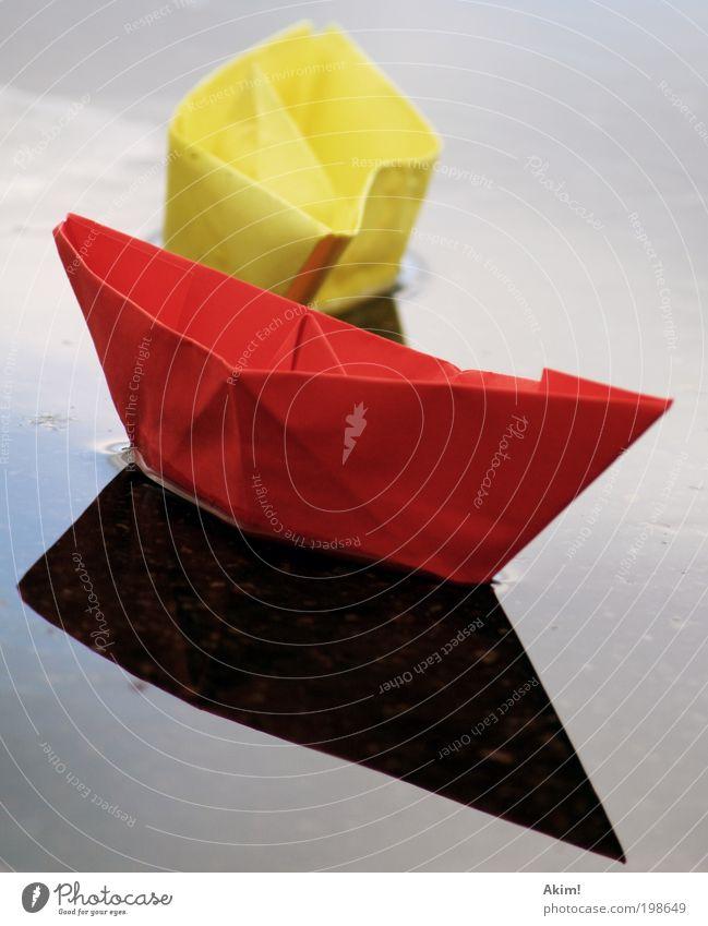 Schiff ahoi! gelb rot Papierschiff Spielzeug Reflexion & Spiegelung See Basteln Spielen gleiten Deutschland Fahne Deutsche Flagge 2010 Farbfoto Außenaufnahme