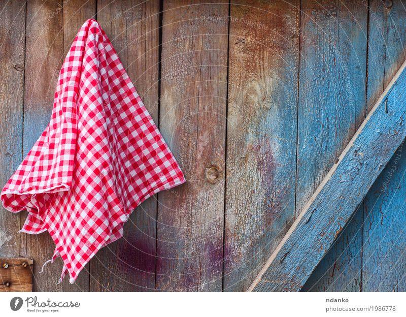 Roter Stoff in einer Zelle, die an einer hölzernen gebrochenen Wand hängt Design Küche Holz alt blau rot weiß Oberfläche Tischwäsche Pfeife Serviette