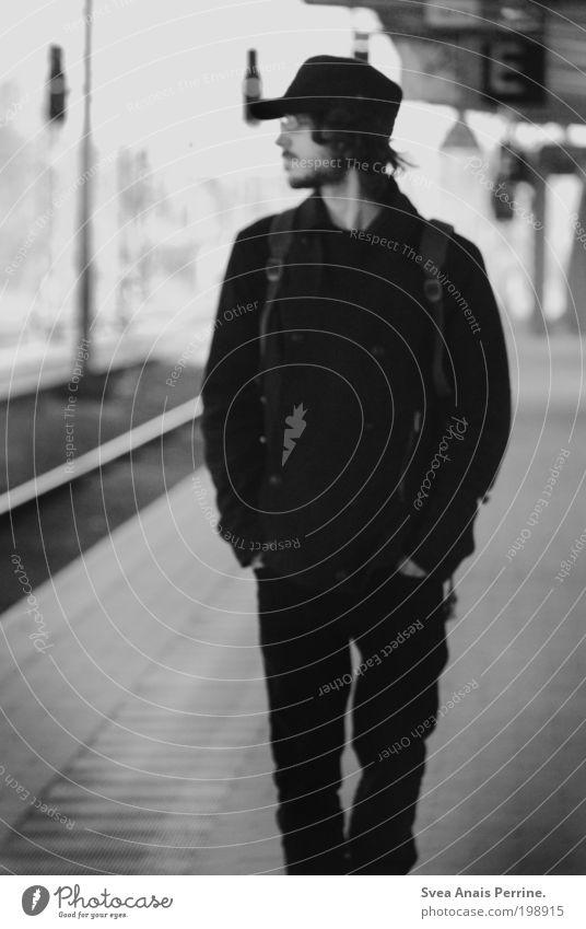 wohlstandskind. maskulin Junger Mann Jugendliche 1 Mensch 18-30 Jahre Erwachsene Bahnhof Fassade Hose Mantel Mütze Blick warten dunkel dünn schwarz weiß Gefühle