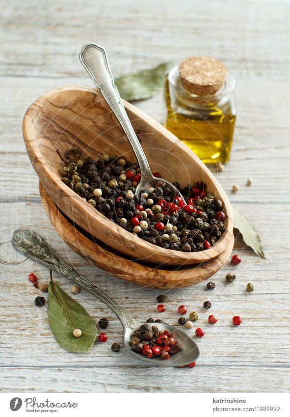 Pfefferkornmischung in einer Schüssel, Lorbeerblättern und Olivenöl Kräuter & Gewürze Öl Schalen & Schüsseln Flasche Löffel Küche grün rot schwarz aromatisch