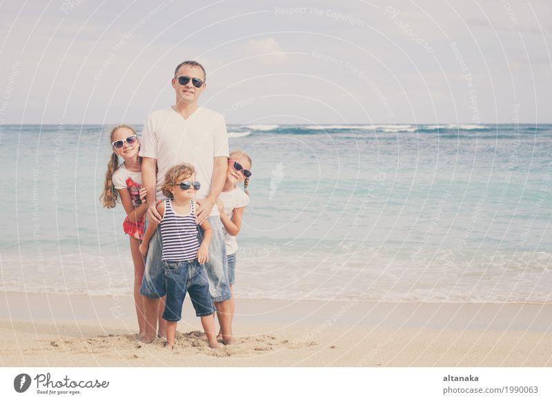 Vater und Kinder, die am Strand zur Tageszeit spielen. Natur Ferien & Urlaub & Reisen Sommer Sonne Hand Meer Erholung Freude Mädchen Erwachsene Leben Lifestyle