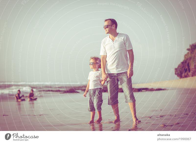 Vater und Sohn spielen am Strand in der Tageszeit. Konzept der freundlichen Familie. Lifestyle Freude Leben Erholung Freizeit & Hobby Spielen