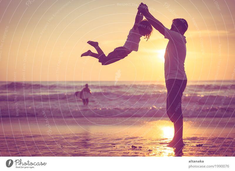 Vater und Sohn, die auf dem Strand zur Sonnenuntergangzeit spielen. Kind Natur Ferien & Urlaub & Reisen Mann Sommer Meer Freude Erwachsene Lifestyle Liebe Sport