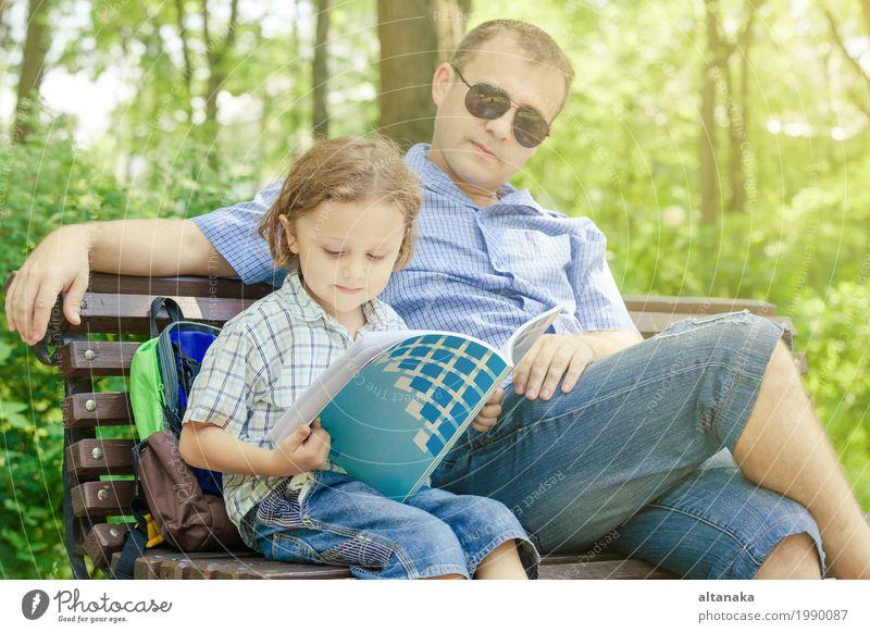 Vater und Sohn, die am Park auf Bank zur Tageszeit spielen. Kind Natur Ferien & Urlaub & Reisen Sommer Sonne Erholung Freude Erwachsene Leben Lifestyle Liebe