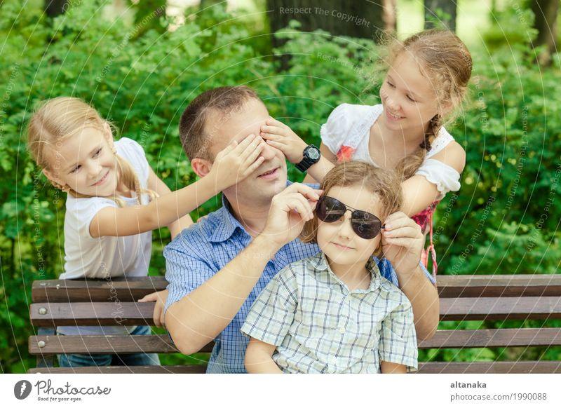 Vater und Kinder, die am Park zur Tageszeit spielen. Mensch Natur Ferien & Urlaub & Reisen Mann Sommer Sonne Freude Mädchen Erwachsene Leben Lifestyle Liebe