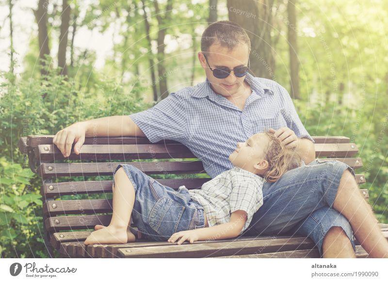 Vater und Sohn, die am Park auf Bank zur Tageszeit spielen. Mensch Kind Natur Ferien & Urlaub & Reisen Mann Sommer Sonne Freude Erwachsene Leben Lifestyle Liebe