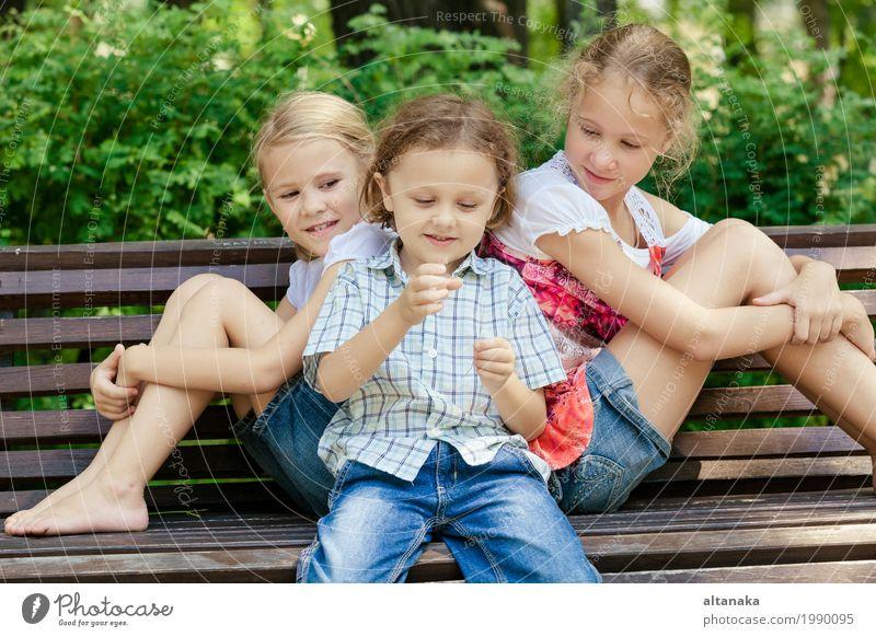Drei glückliche Kinder, die im Park zur Tageszeit spielen. Mensch Natur Ferien & Urlaub & Reisen Sommer schön grün Freude Mädchen Gesicht Lifestyle Liebe Junge