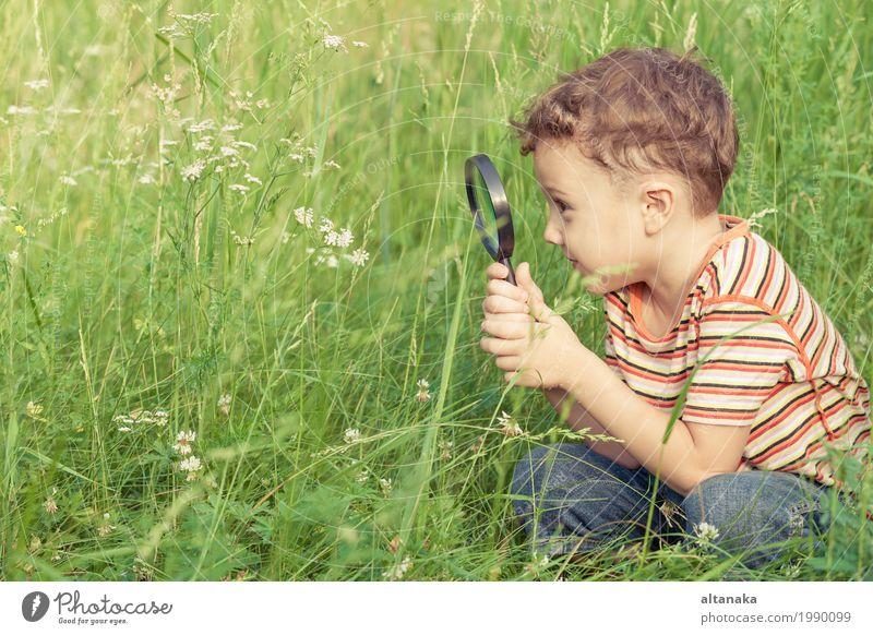 Glücklicher kleiner Junge erforscht die Natur mit Lupe am Tag Lifestyle Freude Gesicht Spielen Sommer Garten Wissenschaften Kind Schule Mensch Kindheit Hand