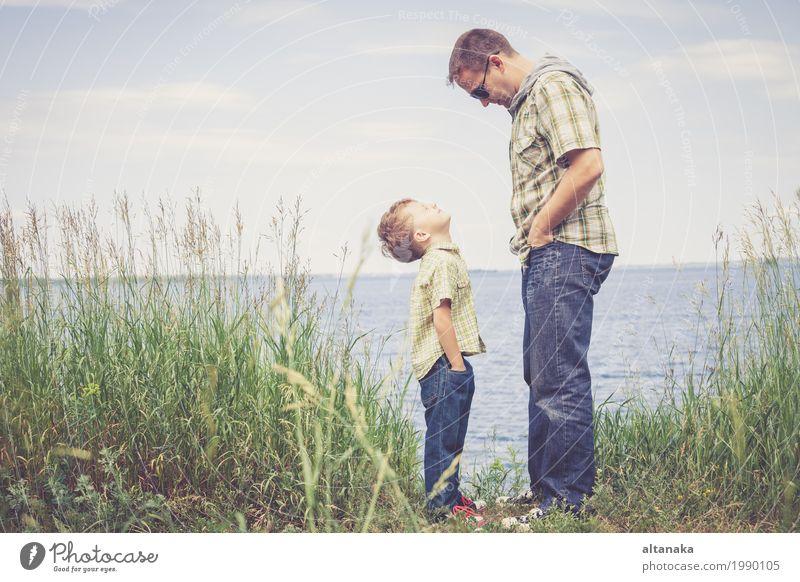 Vater und Sohn, die am Park nahe See zur Tageszeit spielen. Kind Natur Ferien & Urlaub & Reisen Sommer Sonne Erholung Freude Strand Erwachsene Leben Lifestyle