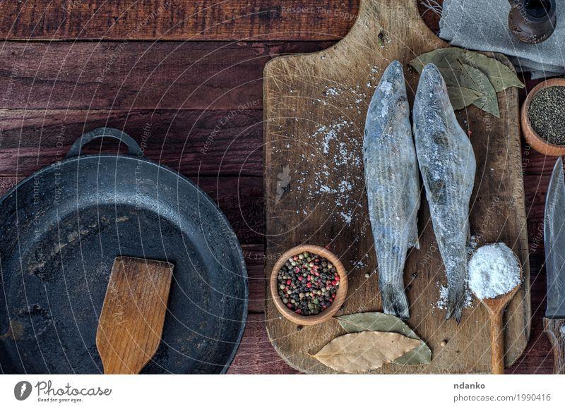 Gefrorener Fisch roch auf dem Küchenbrett Lebensmittel Kräuter & Gewürze Ernährung Essen Pfanne Messer Löffel Tisch Natur Holz Metall Diät frisch oben braun