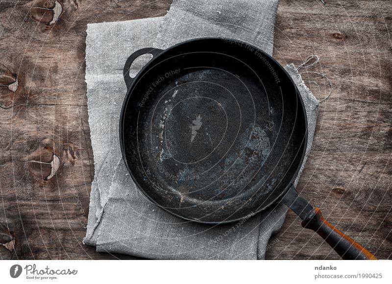 leere schwarze Gusseisenbratpfanne Geschirr Pfanne Tisch Küche Restaurant Stoff Holz Metall oben Sauberkeit braun Tischwäsche Aussicht bügeln braten Utensil Top