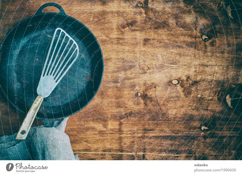 Schwarze leere Bratpfanne mit einer Eisenspachtel Geschirr Pfanne Tisch Küche Restaurant Werkzeug Stoff Holz Metall alt oben Sauberkeit braun schwarz