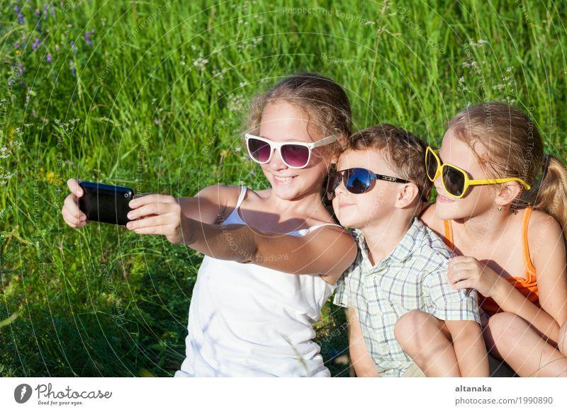 Drei glückliche Kinder, die im Park zur Tageszeit spielen. Mensch Natur Ferien & Urlaub & Reisen Sommer schön grün Freude Mädchen Gesicht Lifestyle Liebe Wiese