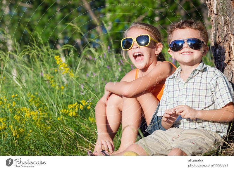 Zwei glückliche Kinder, die nahe dem Baum zur Tageszeit spielen. Mensch Natur Ferien & Urlaub & Reisen Sommer schön grün Freude Mädchen Gesicht Lifestyle Liebe