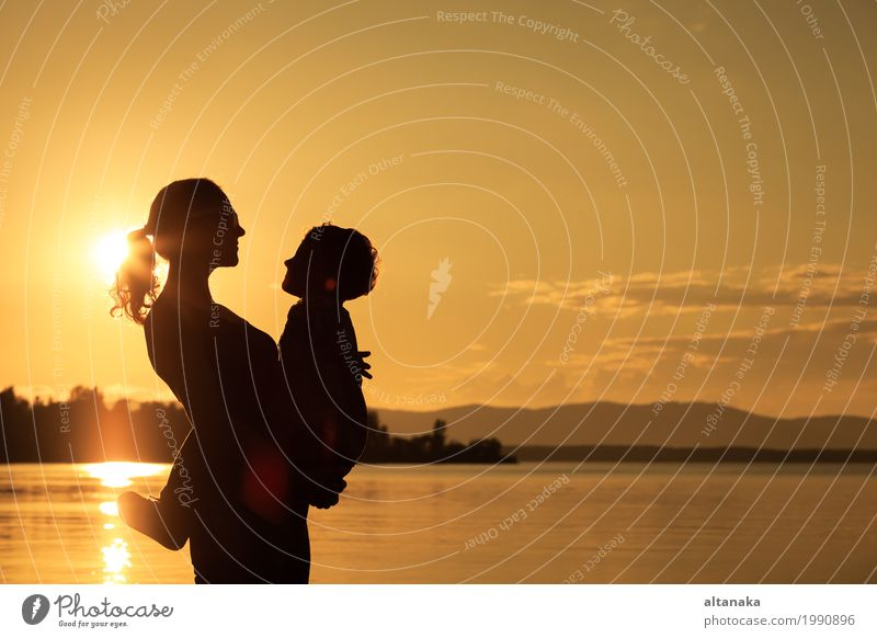 Mutter und Sohn, die auf der Küste von See zur Sonnenuntergangzeit spielen Mensch Kind Frau Natur Ferien & Urlaub & Reisen Mann Sommer Freude Strand