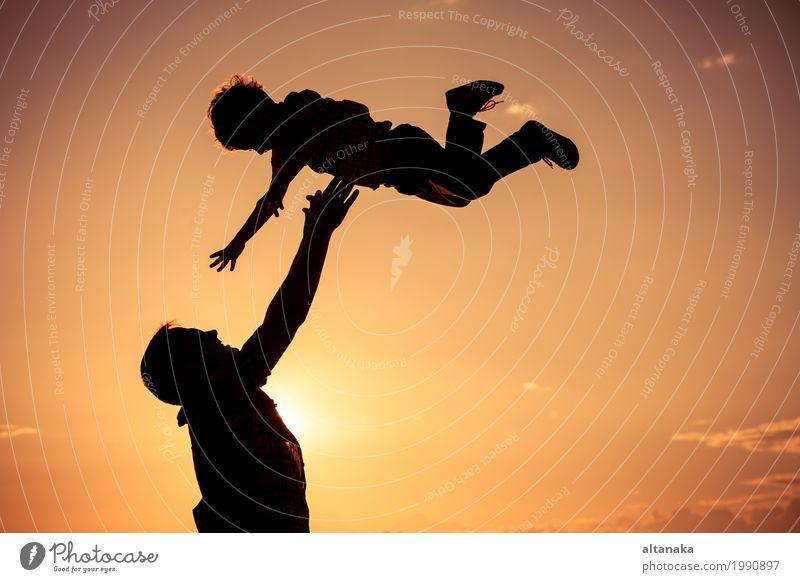 Vater und Sohn, die auf dem Strand zur Sonnenuntergangzeit spielen. Mensch Kind Natur Ferien & Urlaub & Reisen Mann Sommer Freude Berge u. Gebirge Erwachsene