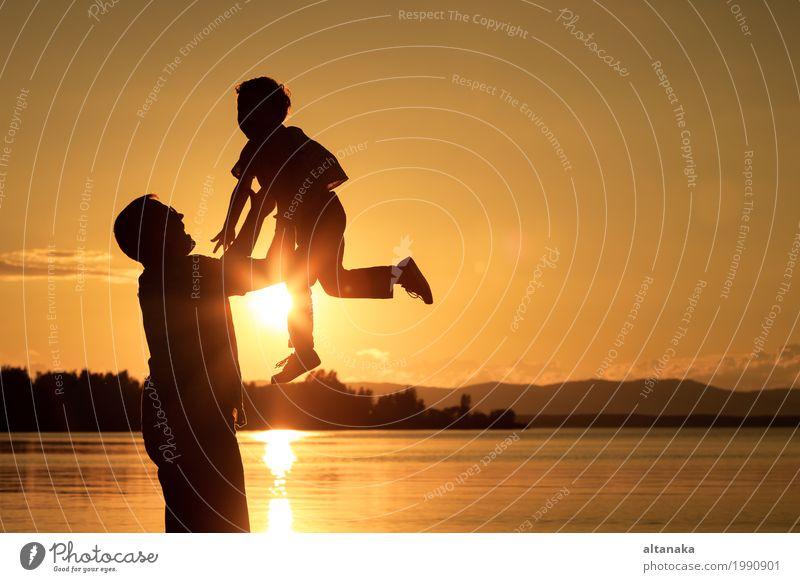 Vater und Sohn, die zur Sonnenuntergangzeit spielen. Mensch Kind Natur Ferien & Urlaub & Reisen Mann Sommer Freude Strand Berge u. Gebirge Erwachsene Lifestyle