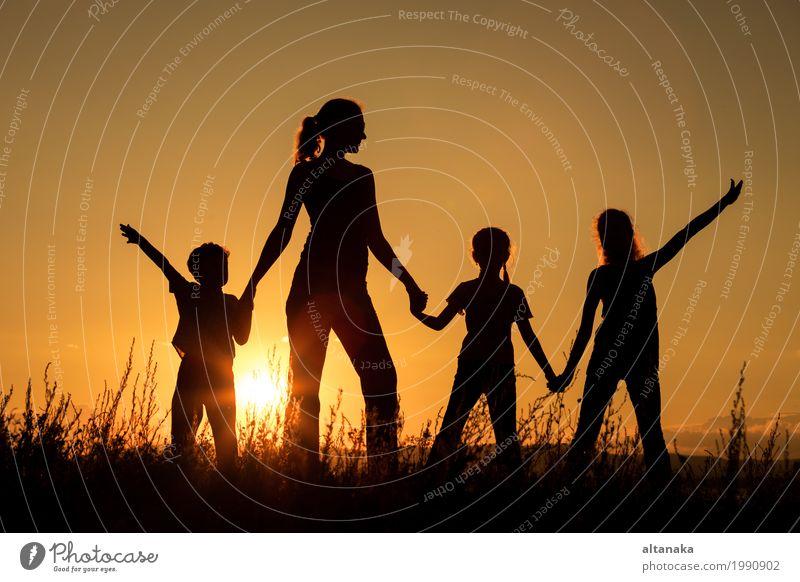 Glückliche Familie, die im Park zur Sonnenuntergangzeit steht. Kind Frau Natur Ferien & Urlaub & Reisen Sommer schön Hand Freude Mädchen Erwachsene Lifestyle