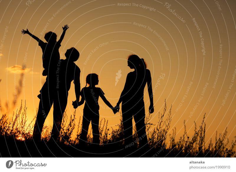 Glückliche Familie, die im Park zur Sonnenuntergangzeit steht. Kind Frau Natur Ferien & Urlaub & Reisen Mann Sommer schön Hand Freude Mädchen Erwachsene