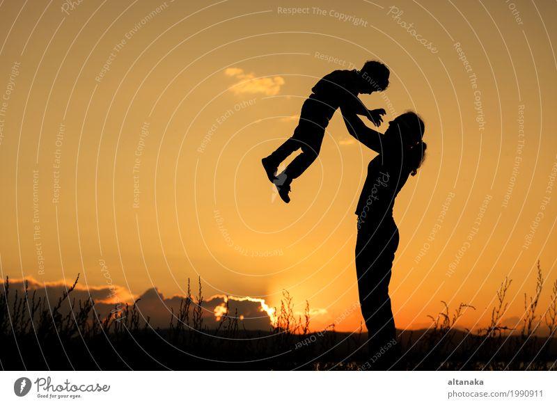 Mutter und Sohn, die zur Sonnenuntergangzeit spielen. Mensch Kind Frau Natur Ferien & Urlaub & Reisen Sommer Freude Strand Berge u. Gebirge Erwachsene Lifestyle