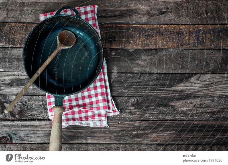 Schwarze Bratpfanne mit einem Löffel auf einer braunen Holzoberfläche Geschirr Pfanne Tisch Küche Restaurant Werkzeug Stoff Metall alt oben Sauberkeit schwarz