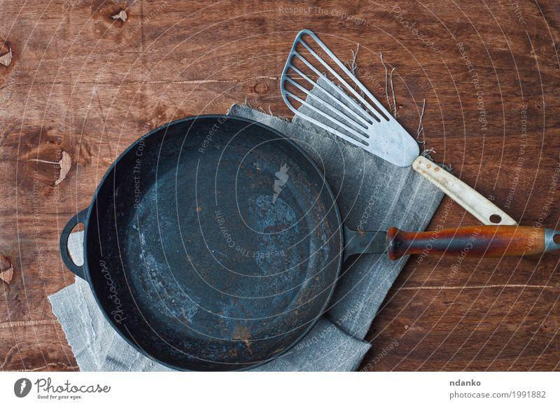 Roheisenschwarzbratpfanne mit Kücheneisenschaufel Geschirr Pfanne Tisch Restaurant Werkzeug Stoff Holz Metall oben Sauberkeit braun Tischwäsche Spachtel Kopie