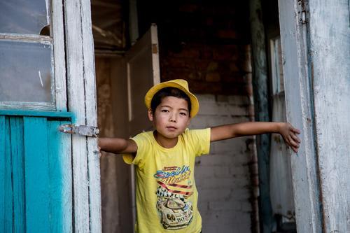 Yellow Fellow Kind Junge Kindheit 1 Mensch 8-13 Jahre Bishkek Kirgisistan Asien Asiate Dorf T-Shirt Hut Armut authentisch Coolness dreckig dunkel einfach frech