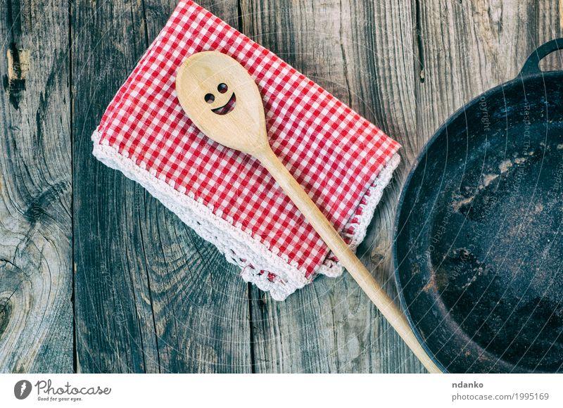 Schwarze Gusseisenbratpfanne mit einem hölzernen Spachtel Geschirr Pfanne Löffel Tisch Küche Restaurant Werkzeug Stoff Kochlöffel Holz Metall oben Sauberkeit