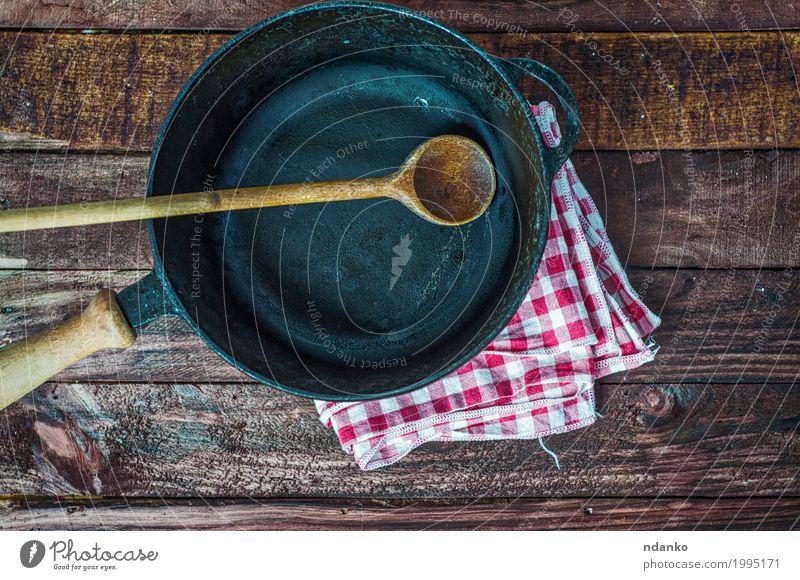 leere schwarze Gusseisenbratpfanne Geschirr Pfanne Löffel Design Tisch Küche Restaurant Stoff Holz Metall oben Sauberkeit braun Tischwäsche Spachtel Aussicht