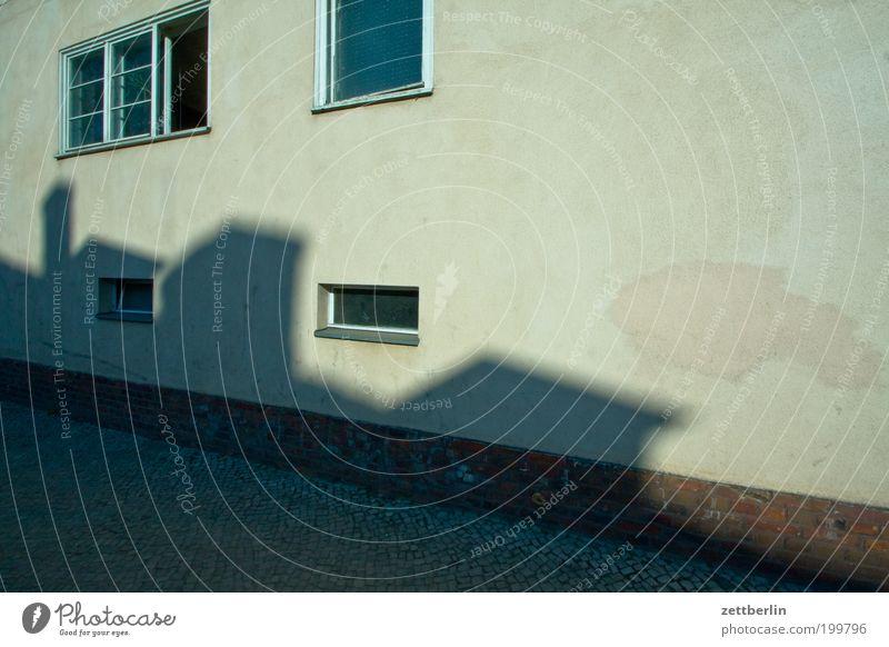 Strukturelles Defizit Haus Wand Gebäude Fenster Vorderseite Fensterfront Schatten Licht Sonne Putz rauhputz Menschenleer Textfreiraum Abend Bildausschnitt