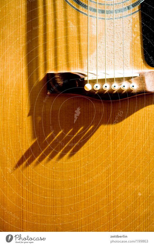 Helle Gitarre Musik Musikinstrument Saite Saiteninstrumente Staub Licht Schatten Holz akustisch Nahaufnahme gelb