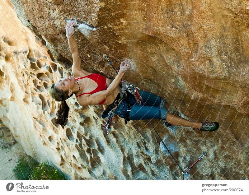 Weibliche Klettererin, die sich an eine Klippe klammert. Abenteuer Klettern Bergsteigen Seil Junge Frau Jugendliche 18-30 Jahre Erwachsene hängen sportlich hoch
