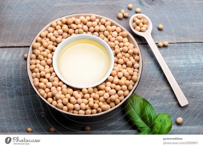Sojabohnenöl-Bohnen und Sojaöl in den Schüsseln auf Holztisch Getreide Ernährung Bioprodukte Vegetarische Ernährung Asiatische Küche Schalen & Schüsseln Löffel