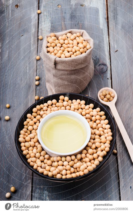 Sojabohnenöl-Bohnen und Sojaöl in den Schüsseln auf Holztisch Ernährung Bioprodukte Vegetarische Ernährung Asiatische Küche Schalen & Schüsseln Löffel Container