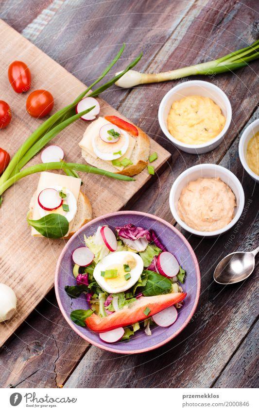 Gesunde Mahlzeit mit Eiern und Gemüse Lebensmittel Salat Salatbeilage Brot Mittagessen Vegetarische Ernährung Diät Schalen & Schüsseln Tisch Holz frisch lecker