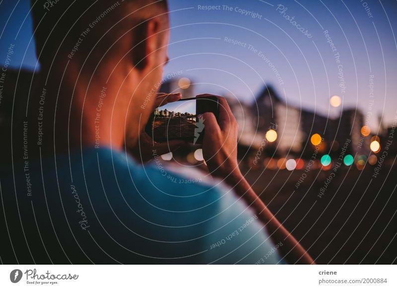 Junger cauacasian Mann, der Foto mit intelligentem Telefon nachts macht Lifestyle Handy PDA Fotokamera Technik & Technologie Unterhaltungselektronik High-Tech