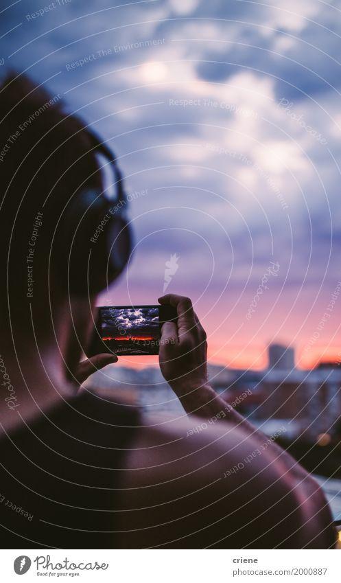 Tragende Kopfhörer des Mannes und Foto mit intelligentem Telefon machend Himmel Jugendliche Sommer Junger Mann Wolken Erwachsene Lifestyle Stimmung Horizont