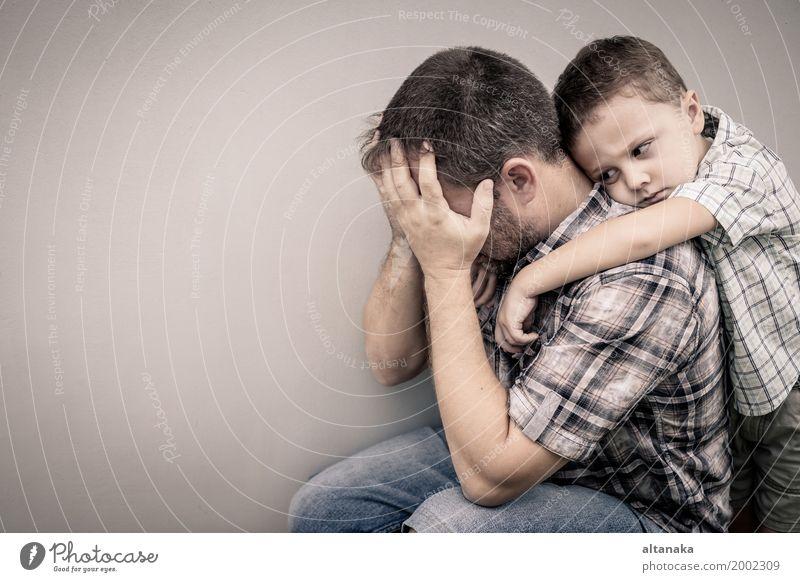 trauriger Sohn, der seinen Vater tagsüber nahe der Mauer umarmt Gesicht Kind Junge Mann Erwachsene Eltern Familie & Verwandtschaft Kindheit Traurigkeit Umarmen