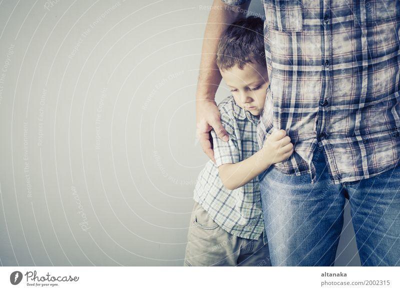 Trauriger Sohn, der seinen Vati nahe Wand umarmt Kind Mann Gesicht Erwachsene Traurigkeit Gefühle Junge Familie & Verwandtschaft Zusammensein Angst Kindheit