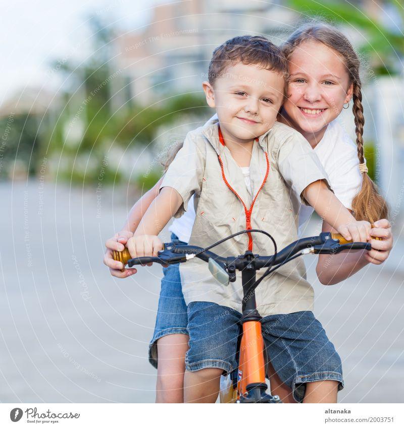 Glückliche Kinder mit dem Fahrrad, das auf der Straße zur Tageszeit steht. Mensch Natur Sommer Freude Mädchen Lifestyle Liebe Gefühle Sport Junge lachen