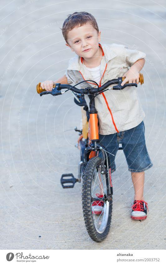 Glücklicher kleiner Junge mit dem Fahrrad, das auf Straße steht Lifestyle Freude Erholung Freizeit & Hobby Abenteuer Sommer Sport Fahrradfahren Kind Mensch Mann