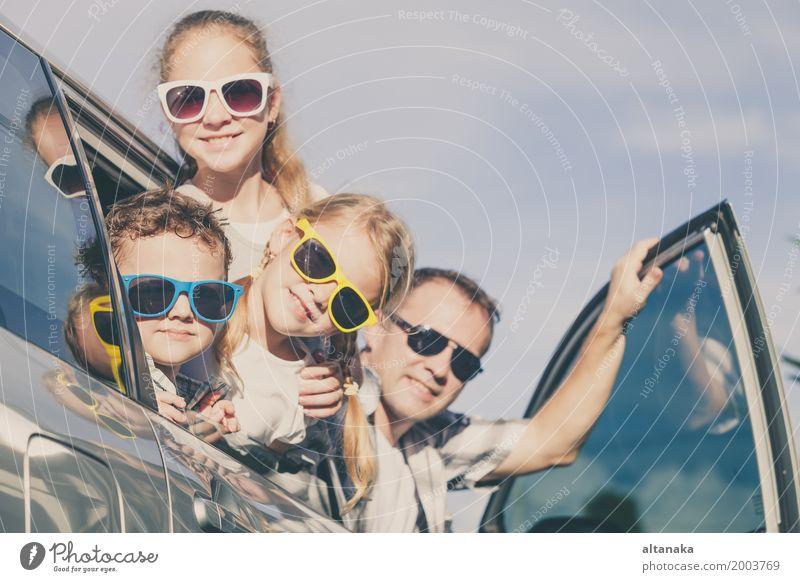 Glückliche Familie, die zur Autoreise an einem sonnigen Tag fertig wird. Lifestyle Freude Freizeit & Hobby Ferien & Urlaub & Reisen Ausflug Abenteuer Freiheit