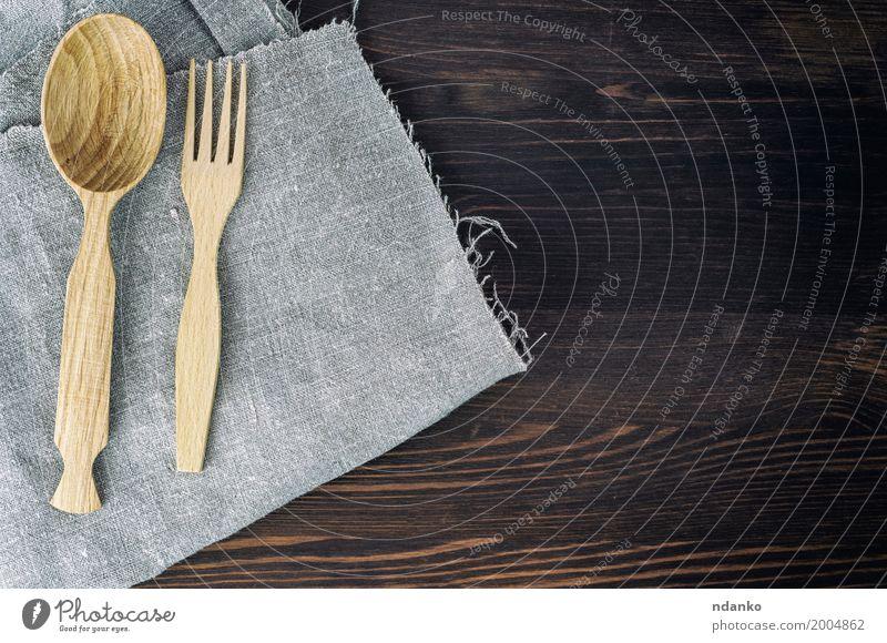 Hölzerner Löffel und Gabel auf grauer Serviette Geschirr Tisch Küche Kochlöffel Holz alt retro braun Speise Utensil Essgeschirr Oberfläche Holzplatte Leerraum