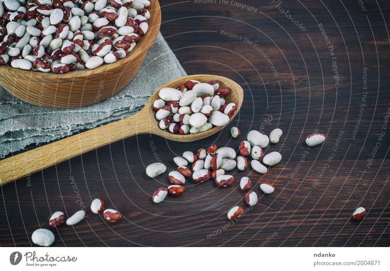 Bohnen in einem hölzernen Löffel auf einem Holztisch Gemüse Ernährung Essen Vegetarische Ernährung Diät Schalen & Schüsseln Menschengruppe frisch lecker braun